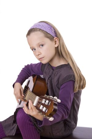 A young girl with long hair is playing guitar. Stock Photo - 12006319
