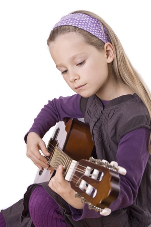 musik: A young girl is playing a guitar.
