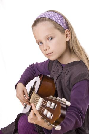 Ein junges Mädchen spielt ihre Gitarre. Standard-Bild - 12031459