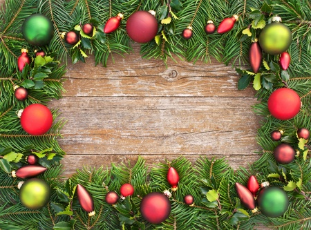 christmas tree branch: frame with christmas tree balls and fir branches on wooden table christmas decoration Stock Photo