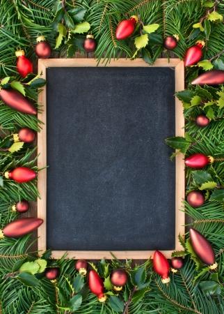 christmas tree branch: blackboard with christmas tree balls and fir branches christmas blackboard Stock Photo