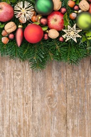 rot und lila Christbaumkugeln, Nüsse, Tannenzweige
