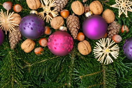 pink and purple christmas tree balls, nuts and fir branches