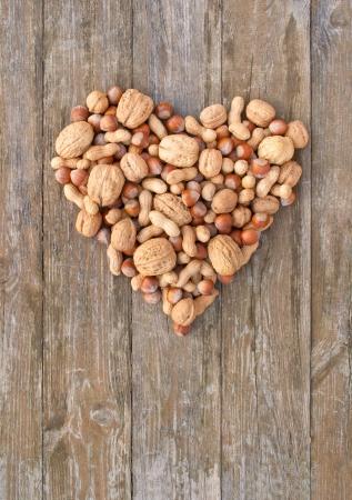 heart with walnuts, peanuts and hazelnuts on wooden background Standard-Bild