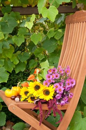 silla de madera: silla de madera con flores, calabazas y casta�as Foto de archivo
