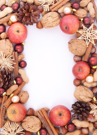 frame with apples, cinnamon, pine cones, nuts and christmas tree balls photo