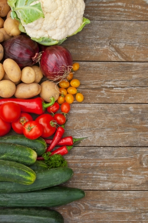 border with vegetables and wooden background