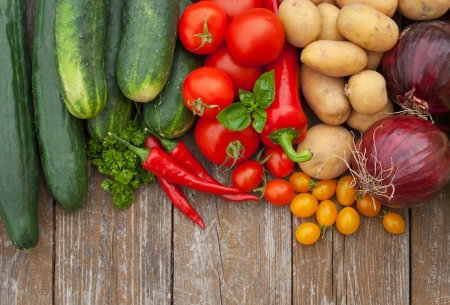 border with vegetables and wooden background photo