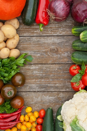 green and purple vegetables: frame with vegetables and wooden background Stock Photo
