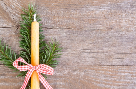 fir branch and yellow candle on wooden ground Standard-Bild
