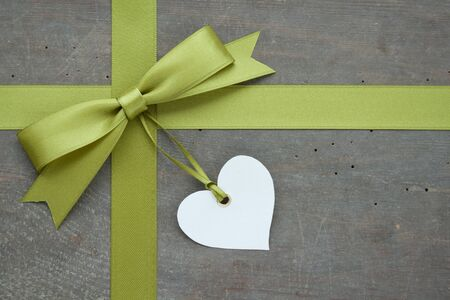 wood textures: green loop with white heart on wooden ground Stock Photo