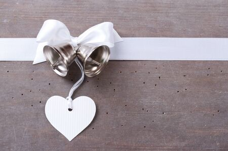 Bells, heart and white loop on wooden ground photo