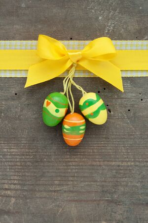 Ostern: yellow loop and easter eggs on wooden ground