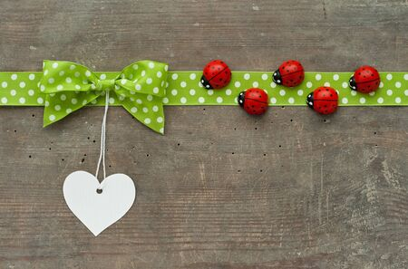 loe: Dotted green loop, lady bugs and white heart on wooden ground Stock Photo