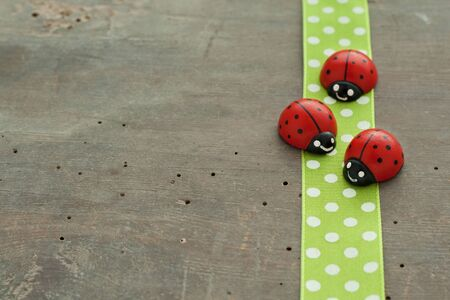 Dotted green tape and lady bugs on wooden ground Stock Photo - 17567878