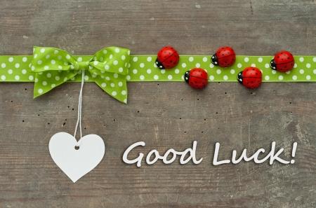 buena suerte: Tarjeta con lazo verde de puntos, mariquitas y corazón blanco Foto de archivo