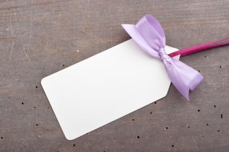 Label mit violetten Schleife auf hölzernen Boden Standard-Bild