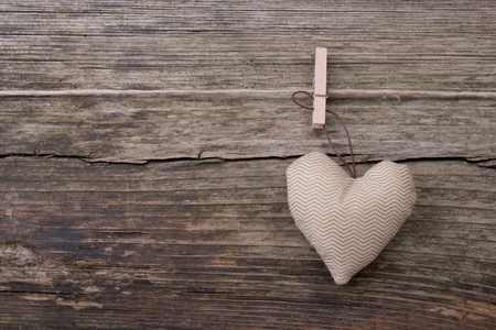 heart with clamps on wooden ground photo