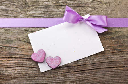 violet loop, hearts and card on wooden ground photo