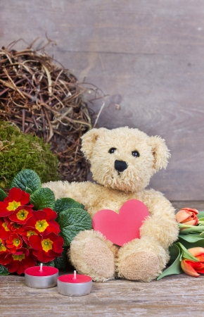valentine s day teddy bear: teddy  bear with flowers, candles and heart Stock Photo