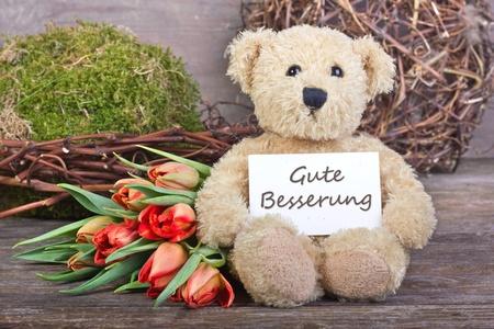 Teddybär mit Blumen und Karte mit Schriftzug get well Standard-Bild - 17996276