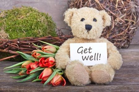 Teddybär mit Blumen und Karte mit Schriftzug get well Standard-Bild - 17996305