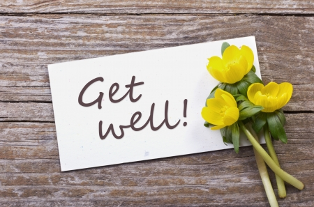 yellow blossoms and white card with lettering get well