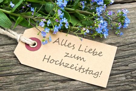 aniversario de boda: flores de color azul y tarjeta del aniversario de boda