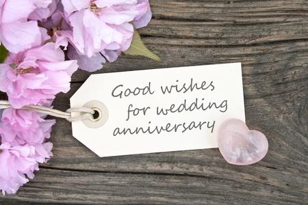 aniversario de boda: flores de color rosa y tarjeta del aniversario de boda