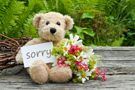 teddy bear with flowers and card with lettering sorry Foto de archivo