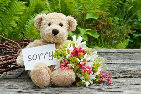 teddybeer met bloemen en kaart met letters spijt Stockfoto
