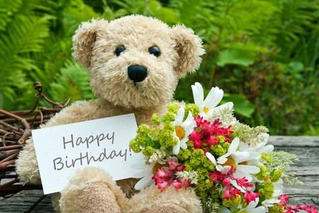orsacchiotto con fiori e carta di compleanno Archivio Fotografico