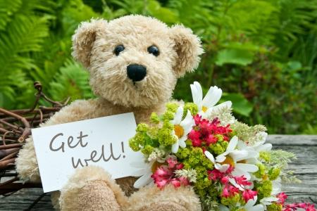 oso de peluche con flores y tarjetas con letras consiga bien Foto de archivo