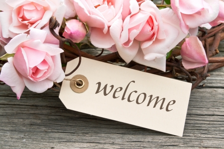 pink roses and label with lettering welcome