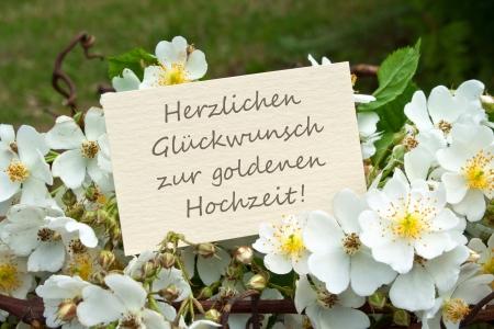 aniversario de boda: rosas blancas y tarjeta del aniversario de bodas de oro