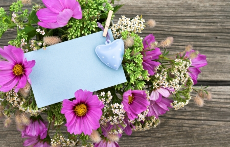 pink flowers with card and heart on wooden ground photo