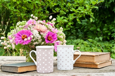 two coffee mugs old books and flowers