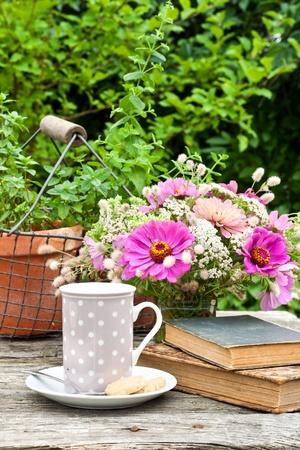 tarde de cafe: taza de café, libros antiguos y flores
