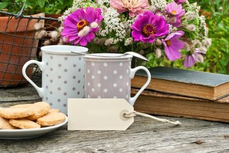 twee koffiemokken oude boeken en bloemen Stockfoto