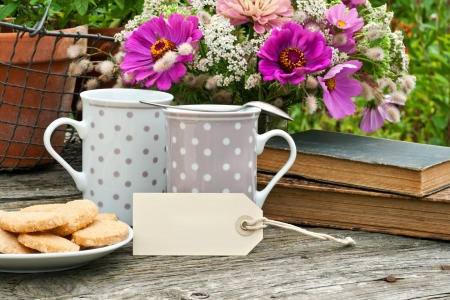 coffee hour: two coffee mugs old books and flowers