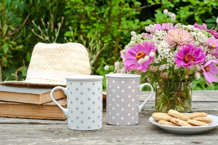 coffee hour: two mugs, old books, straw hat and flowers