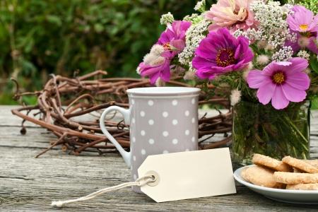tarde de cafe: taza de café, galletas y flores Foto de archivo