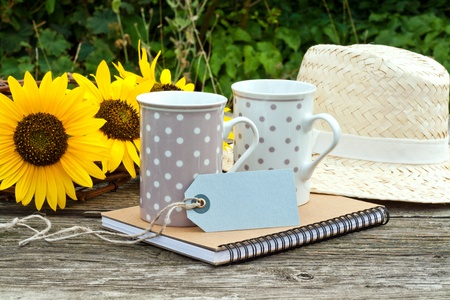two coffee mugs, sunflowers and straw hat photo