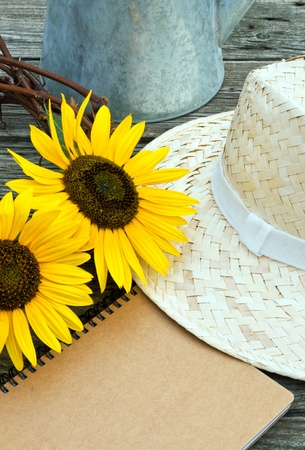 sunflowers, straw hat and note book on wooden table photo