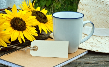 coffee mug, sunflowers and note book on wooden table photo