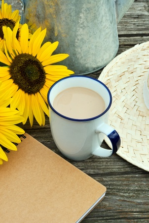 coffee mug , straw hat, sunflowers and note book on wooden table photo