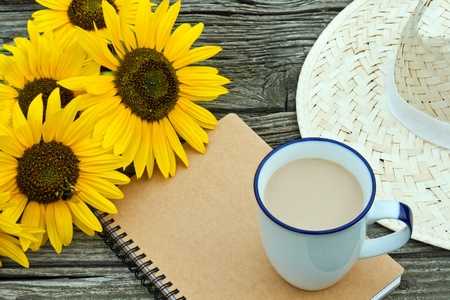 coffee mug, straw hat sunflowers and note book on wooden table photo