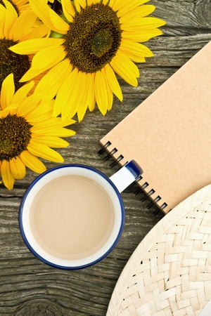 note book: tazza di caff�, girasoli e nota libro su tavola di legno