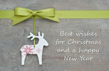 merry christmas text: tarjeta de Navidad con renos y el arco verde Foto de archivo