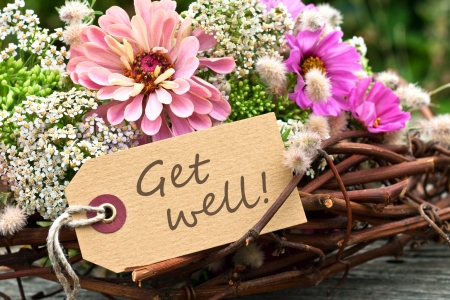 pink flowers and card with lettering get well Stock Photo